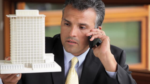 CU Architect Talking on Cell Phone, Looking at Model Building in Office / Richmond, Virginia, USA