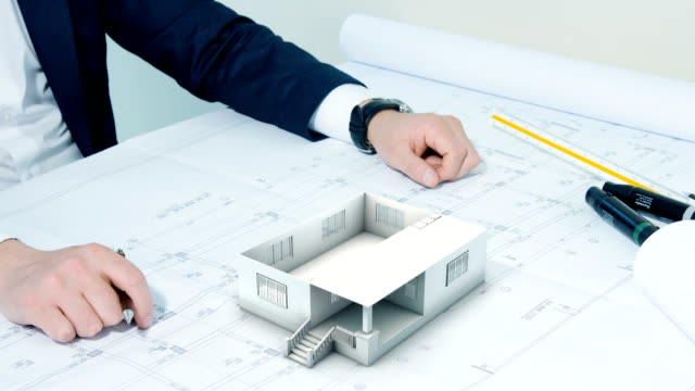 Architect working on table with plans and building construct