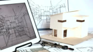Architect working with house model & blueprints