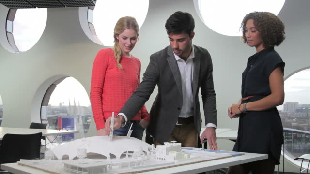 Architects giving presentation and studying maquette