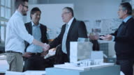 DS Architects shaking hands with investor next to the design model