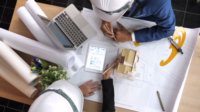 Architects Team defining the design details with Blueprint and Architectural Model, Directly Above