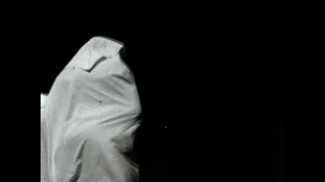 Archival footage of Shadow People representing the religious occult / people draped in bed sheets