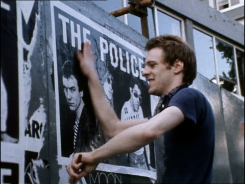 Archive footage of punks on Kings Road Young Stewart Copeland pasting 'The Police' posters to wall / Sting looking casual watching Copeland do the...
