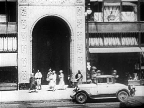 B/W 1929 archway of building with pedestrians + cars on city street in foreground / newsreel