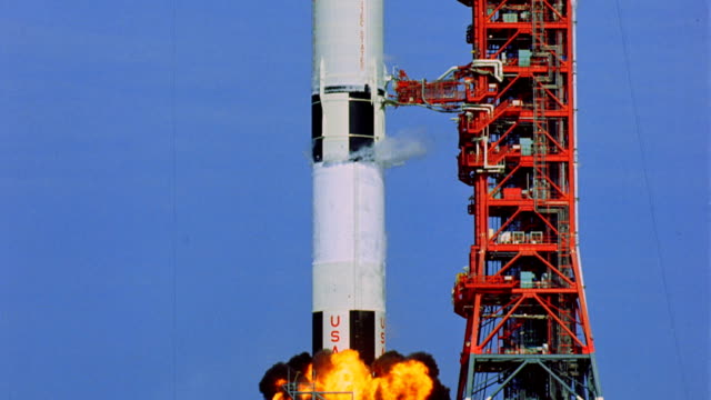 arm braces pulling away from Apollo 11 rocket on launch pad rocket taking off