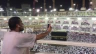 Arm outstretched Abdul Rahman sweeps his mobile phone across the vista of Mecca the Great Mosque dazzling in the sun so his son in Tanzania can...