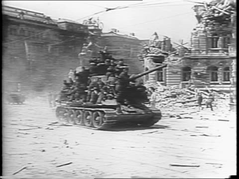 Armed civilians fire on German soldiers / man shoots gun while dead man lies in street nearby / man pulls body in street / Russian Red Army rolls...