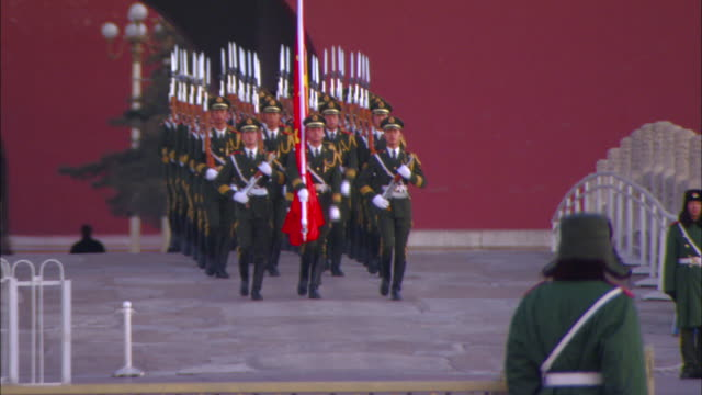 Armed guards march out of the North Gate of the Forbidden City and across Tiananmen Square.