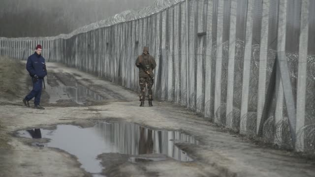 Armed members of the Hungarian military patrol by the razor wired topped security fence on the HungarianSerbian border near Roszke Hungary on...
