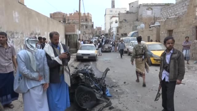 Armed men from Yemen's Houthi group inspect the wreckage after suicide car bombing attack outside the al Faid masjid in Nuqum region in Yemeni...