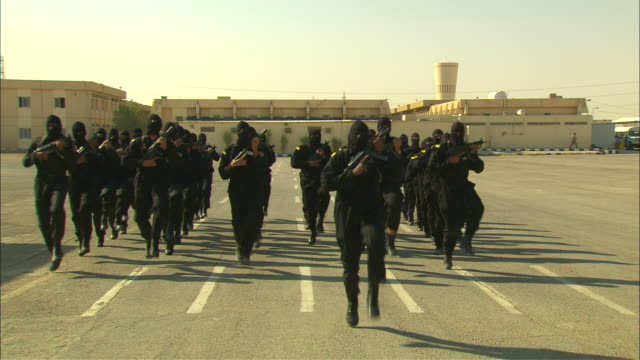 Armed soldiers in black masks march on a military base in Saudi Arabia.