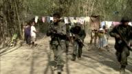 Armed soldiers walk through a village.