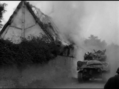 Armored vehicle moving past burning village house LA Allied US Sherman medium tank moving over town rubble w/ bullet bomb damaged building walls...