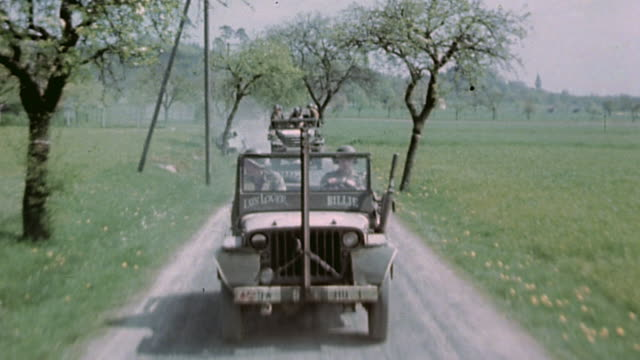 S Army convoy of Jeeps and infantryladen trucks driving on country road / Germany