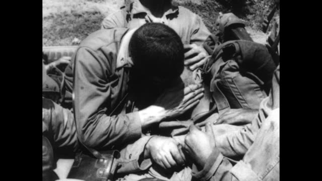 VS Army medics in the field administering blood from bottles priest kneels over man on stretcher and anther soldiers crouches over comrade patting...