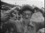 Army nurses stand in field practice putting on their gas masks / nurses in masks walk into a fog and maneuver trenches and hills of dirt / nurses run...