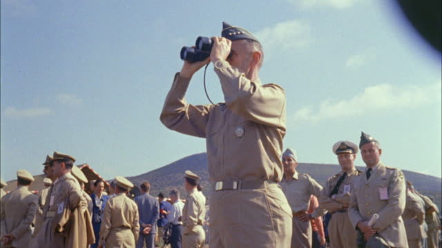 1967 LA MS Army officer looking through binoculars standing amongst other soldiers outdoors