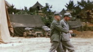S Army officers inspecting base camp and walking past large tent / Korea