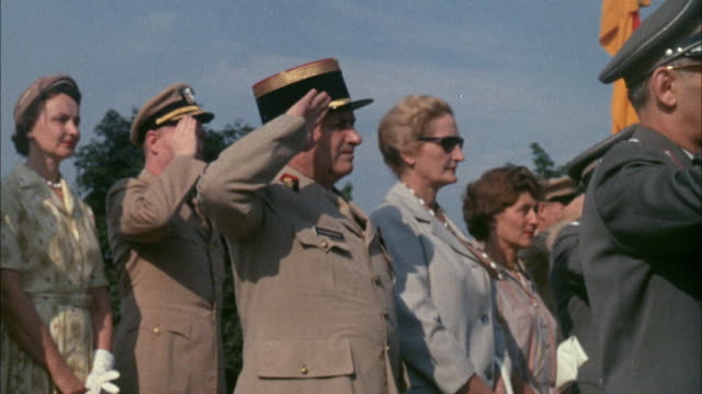 1967 MS Army officers saluting, standing next to women outdoors