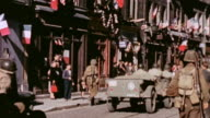 S Army on feet and driving Jeeps liberating a town decorated with tricolor bunting and flags and GIs walking arminarm with grateful women / Lyons...