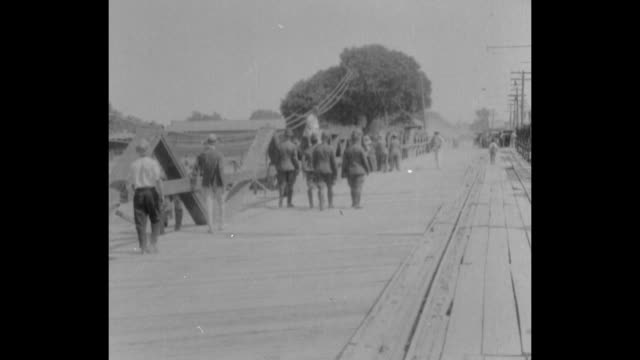 Army personnel including General George Bell Jr walk toward International Bridge / Mexican soldiers and captured Buffalo Soldiers approach stop / MS...