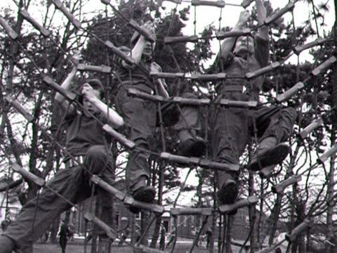 Army recruits climb over netting at an army training centre