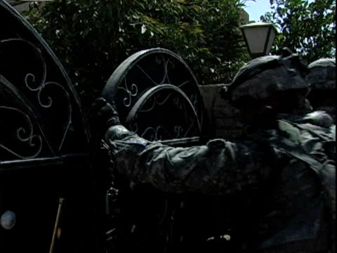 Army soldiers breaking lock on gate and entering house during patrol / Baghdad Iraq / AUDIO