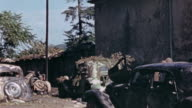 S Army soldiers looking at bombed and wrecked civilian cars / France