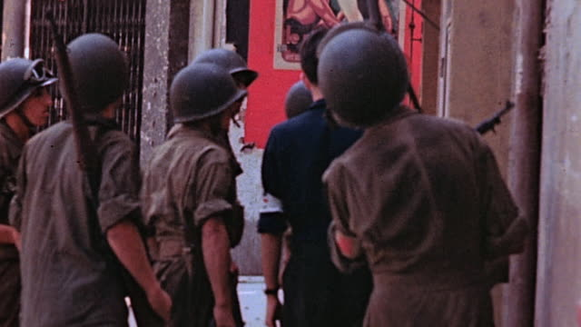 S Army soldiers on city street with French flags waving and liberated civilians riding in back of open truck and hanging out back of car / Marseilles...