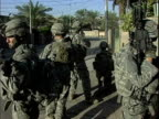 Army soldiers standing guard outside house during patrol / Baghdad Iraq / AUDIO