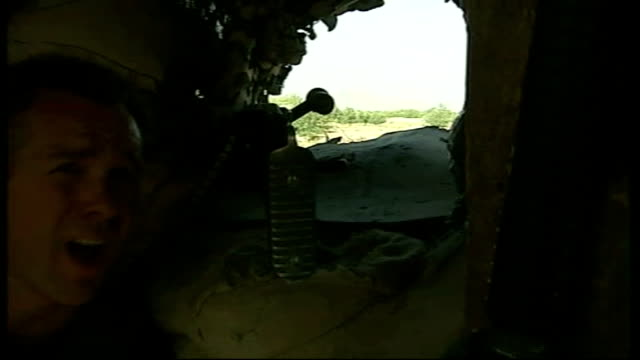 US Army's 101st Airborne Division work with Afghan troops outside Kandahar AFGHANISTAN Kandahar province EXT Back view US soldier looking through gun...