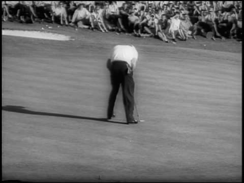 Arnold Palmer putting ball into hole then shaking hands with Ken Venturi / Masters
