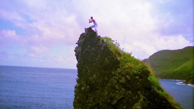 AERIAL around man standing on summit of rock island in ocean doing Tai Chi / Hawaii