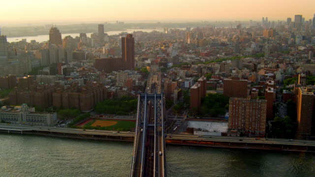 MEDIUM AERIAL around Manhattan Bridge with Brooklyn Bridge and cityscape in background at sunset