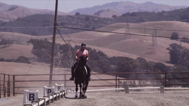 Arriba Vista Ranch, dressage ring, Linda cantors towards camera, circles away
