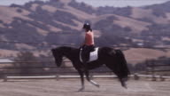 Arriba Vista Ranch, dressage ring, Linda circles horse in center of ring, then rides toward camera