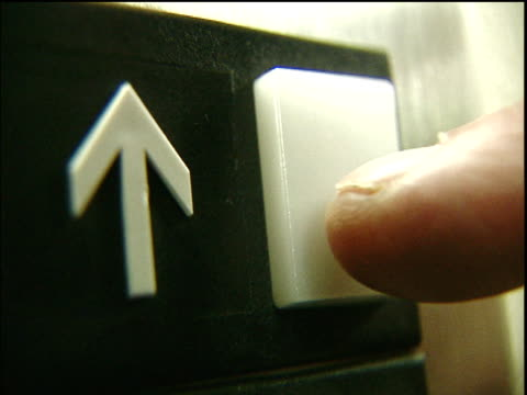 Arrow points upwards next to elevator button, finger presses button to summon elevator.