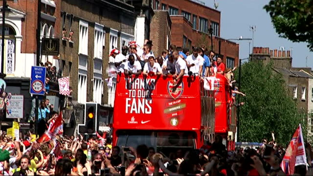 Arsenal FA Cup victory parade Various of Arsenal players waving to fans from opentopped bus as it moves slowly along towards Town Hall/ Arsenal...
