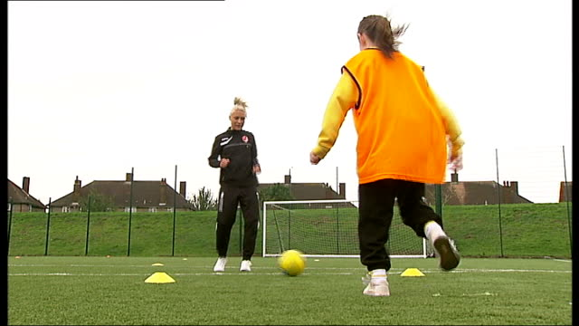Arsenal Ladies prepare for Continental Cup Final ENGLAND London Edgeware EXT Various shots Megan Harris training with anonymous primary school girl...