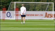 Arsenal open training prior to match against Benfica Various GVs of players jogging on pitch / Wenger walking and watching kicking ball / more of...