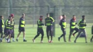 Arsenal training Players along for jog led by Laurent Koscielny / Arsenal team jogging and warming up including Mesut Ozil / Players doing stretches
