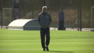 Hertfordshire Colney EXT Arsene Wenger onto training pitch alone good shots/ Various of Arsenal players onto training pitch and shaking hands with...