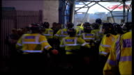 Coin inquiry LIB WALES Cardiff Ninian Park Riot police running away to enter stadium Various fans along outside ground