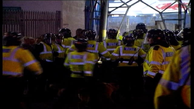Coin inquiry LIB WALES Cardiff Ninian Park Riot police running away to enter stadium GV Scuffling among fans outside stadium MS Fans along