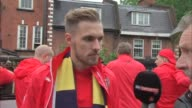 Arsenal victory parade from bus Aaron Ramsey interview / various of players on bus and fans lining the route including Manager Arsene Wenger holding...