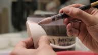 Art Studio. Young Man Painting Porcelain Cup in Art Studio.