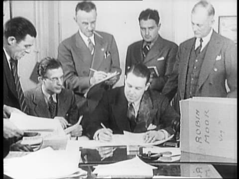 Arthur R Lewis Jr seated at desk with officials / Lewis looking at ship manifest / Lewis reading from manifest to officials / close up of Lewis...