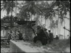 Artillery regiment firing cannons US Marines advancing inland across fields on Los Negros Island World War II WWII Pacific Front New Guinea