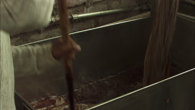 Artisans wash fabric in a large vat. Available in HD.